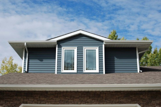 exterior shot of the second storey windows of a house with blue siding